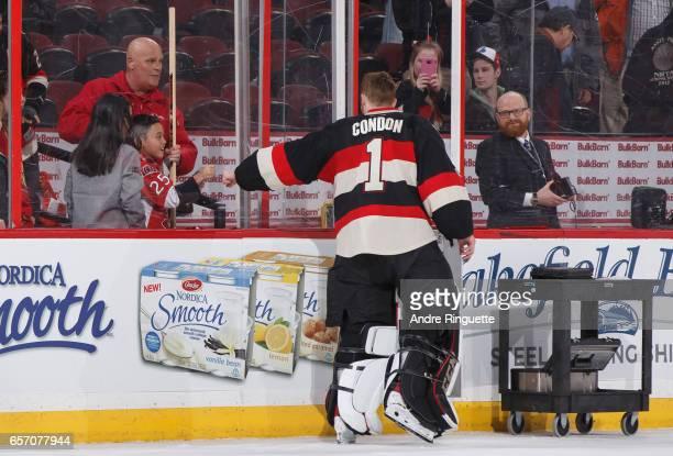 Mike Condon of the Ottawa Senators fistbumps a young fan after being named the 1st star of the game after a win against the Pittsburgh Penguins at...