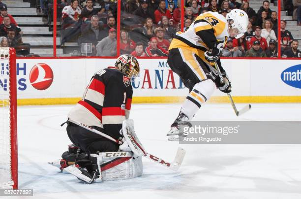 Mike Condon of the Ottawa Senators guards his net as Chris Kunitz of the Pittsburgh Penguins jumps in the air while screening on the play at Canadian...