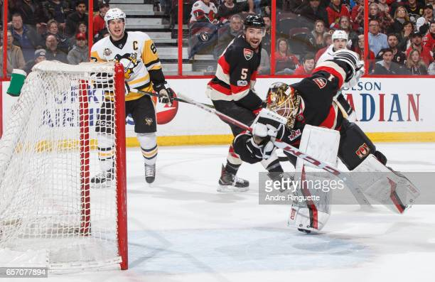 Mike Condon of the Ottawa Senators makes a desperation blocker save with his back turned to the play as teammate Cody Ceci and Sidney Crosby of the...
