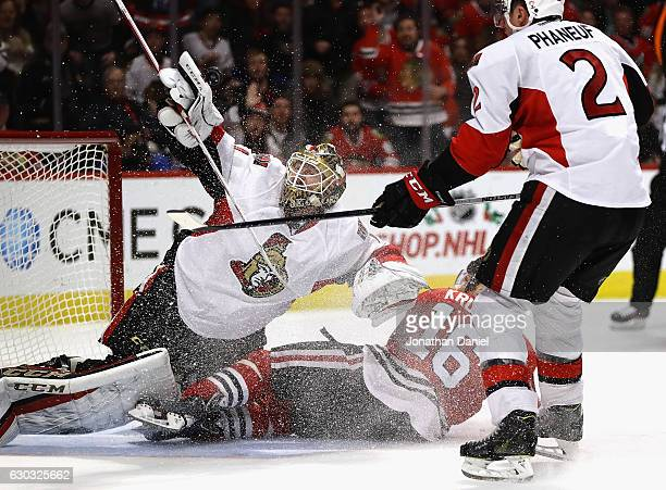 Mike Condon of the Ottawa Senators makes a save off of his gloves as Marcus Kruger of the Chicago Blackhawks crashes into him after being shoved down...