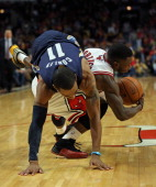 Mike Conley of the Memphis Grizzles falls over Nate Robinson of the Chicago Bulls at the United Center on January 19 2013 in Chicago Illinois The...