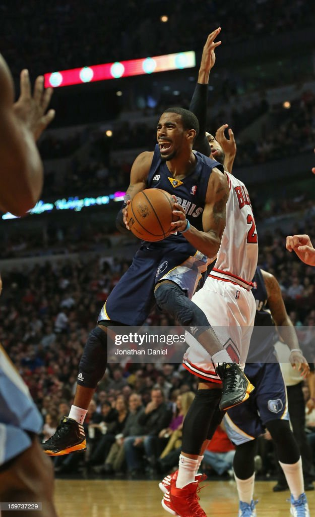 Mike Conley #11 of the Memphis Grizzles leaps to pass around <a gi-track='captionPersonalityLinkClicked' href=/galleries/search?phrase=Taj+Gibson&family=editorial&specificpeople=4029461 ng-click='$event.stopPropagation()'>Taj Gibson</a> #22 of the Chicago Bulls at the United Center on January 19, 2013 in Chicago, Illinois.