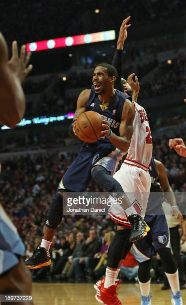 Mike Conley of the Memphis Grizzles leaps to pass around Taj Gibson of the Chicago Bulls at the United Center on January 19 2013 in Chicago Illinois...