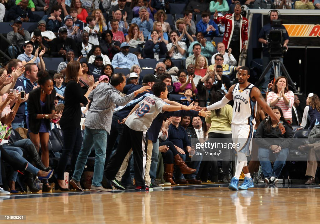 Mike Conley #11 of the Memphis Grizzlies celebrates with fans in the game against the Houston Rockets on March 29, 2013 at FedExForum in Memphis, Tennessee.