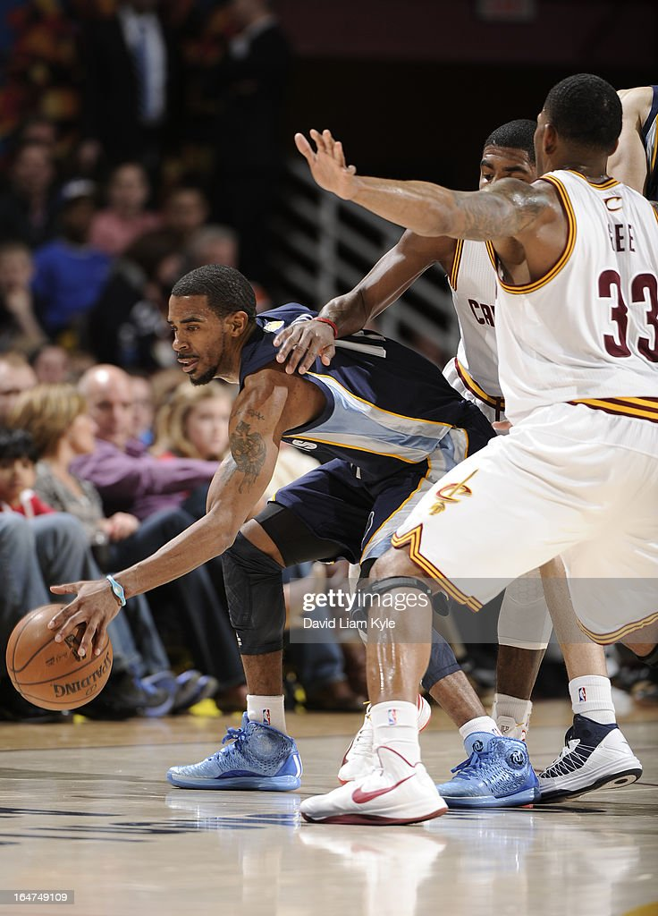 Mike Conley #11 of the Memphis Grizzlies controls the ball under pressure by <a gi-track='captionPersonalityLinkClicked' href=/galleries/search?phrase=Kyrie+Irving&family=editorial&specificpeople=6893971 ng-click='$event.stopPropagation()'>Kyrie Irving</a> #2 and <a gi-track='captionPersonalityLinkClicked' href=/galleries/search?phrase=Alonzo+Gee&family=editorial&specificpeople=801443 ng-click='$event.stopPropagation()'>Alonzo Gee</a> #33 of the Cleveland Cavaliers at The Quicken Loans Arena on March 8, 2013 in Cleveland, Ohio.