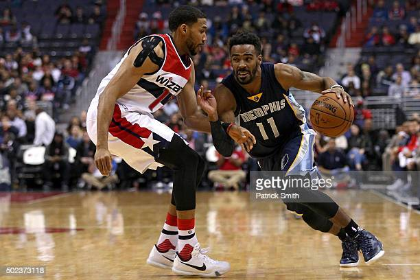 Mike Conley of the Memphis Grizzlies dribbles by Garrett Temple of the Washington Wizards in the first half at Verizon Center on December 23 2015 in...