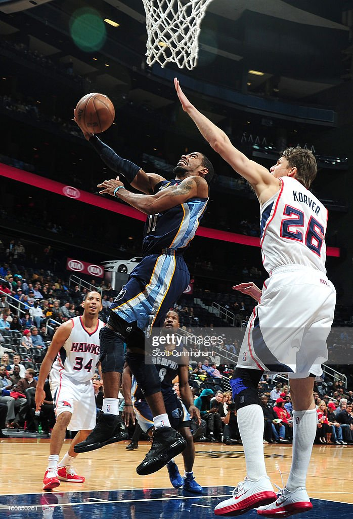 Mike Conley #11 of the Memphis Grizzlies goes to the basket against <a gi-track='captionPersonalityLinkClicked' href=/galleries/search?phrase=Kyle+Korver&family=editorial&specificpeople=202504 ng-click='$event.stopPropagation()'>Kyle Korver</a> #26 of the Atlanta Hawks during the game between the Atlanta Hawks and the Memphis Grizzlies on February 6, 2013 at Philips Arena in Atlanta, Georgia.