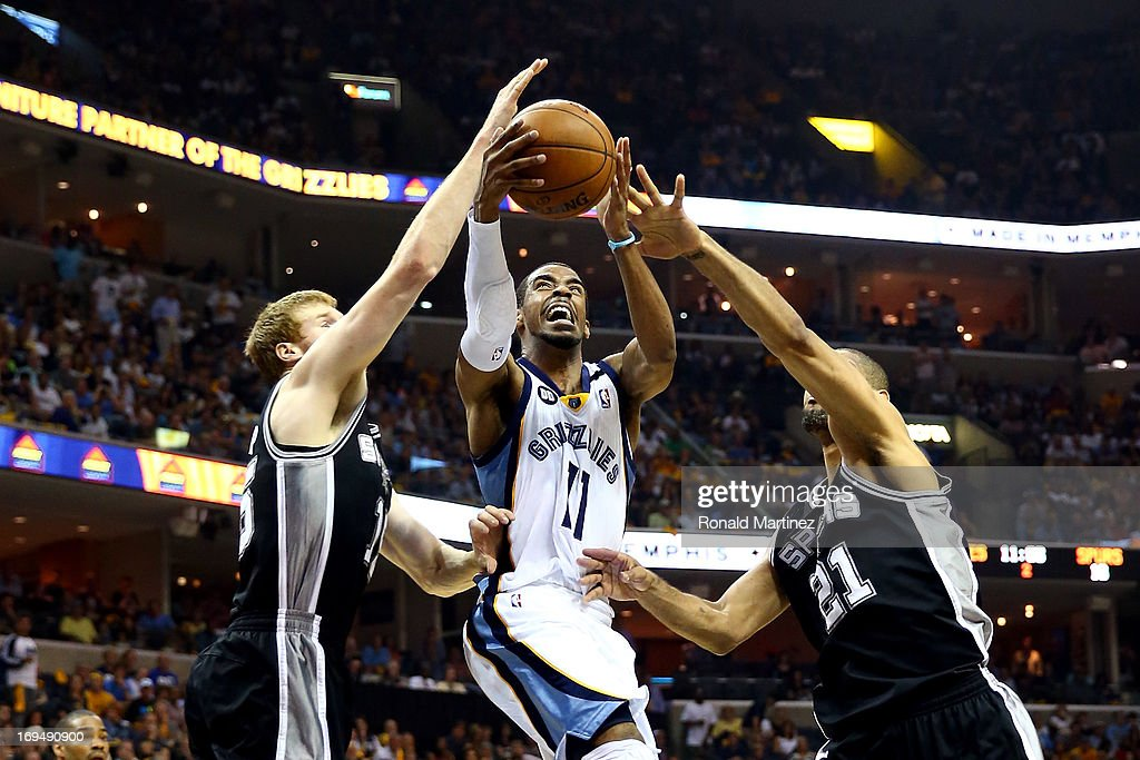 Mike Conley #11 of the Memphis Grizzlies goes up for a shot between <a gi-track='captionPersonalityLinkClicked' href=/galleries/search?phrase=Matt+Bonner&family=editorial&specificpeople=203054 ng-click='$event.stopPropagation()'>Matt Bonner</a> #15 and <a gi-track='captionPersonalityLinkClicked' href=/galleries/search?phrase=Tim+Duncan&family=editorial&specificpeople=201467 ng-click='$event.stopPropagation()'>Tim Duncan</a> #21 of the San Antonio Spurs in the first half during Game Three of the Western Conference Finals of the 2013 NBA Playoffs at the FedExForum on May 25, 2013 in Memphis, Tennessee.