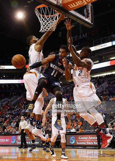 Mike Conley of the Memphis Grizzlies makes a leaping pass inbetween Markieff Morris and Eric Bledsoe of the Phoenix Suns during the second half of...