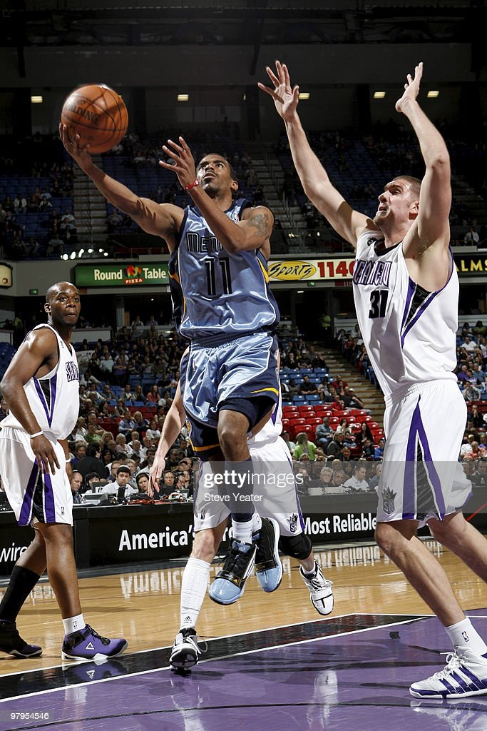 Mike Conley #11 of the Memphis Grizzlies takes the ball to the basket against Spencer Hawes #31 of the Sacramento Kings on March 22, 2010 at ARCO Arena in Sacramento, California.