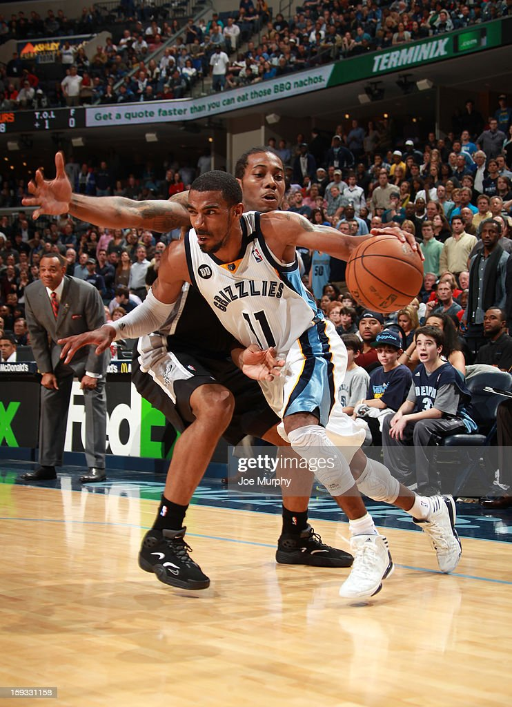 Mike Conley #11of the Memphis Grizzlies drives to the basket against Kawhi Leonard #2 of the San Antonio Spurs on January 11, 2013 at FedExForum in Memphis, Tennessee.