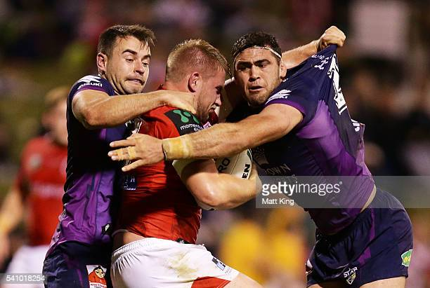 Mike Cooper of the Dragons is tackled during the round 15 NRL match between the St George Illawarra Dragons and the Melbourne Storm at WIN Stadium on...
