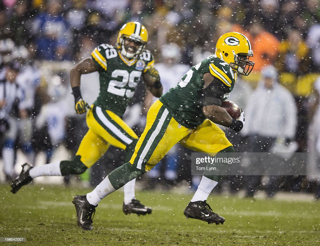 Mike Daniels #76 of the Green Bay Packers scoops up a fumble and runs for a touchdown as teammate Casey Hayward #29 follows at Lambeau Field on December 9, 2012 in Green Bay, Wisconsin.