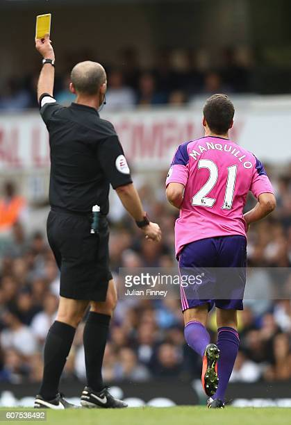 Mike Dean gives Javier Manquillo of Sunderland a yellow card during the Premier League match between Tottenham Hotspur and Sunderland at White Hart...