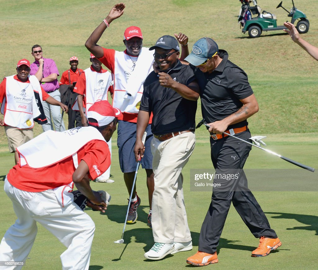 Mike Dladla (2nd R) is congratulated by team-mate Herschelle Gibbs after sinking the winning putt during Round 2 of the Gary Player Invitational presented by Coca-Cola at The Lost City Golf Course on November 17, 2013 in Sun City, South Africa.
