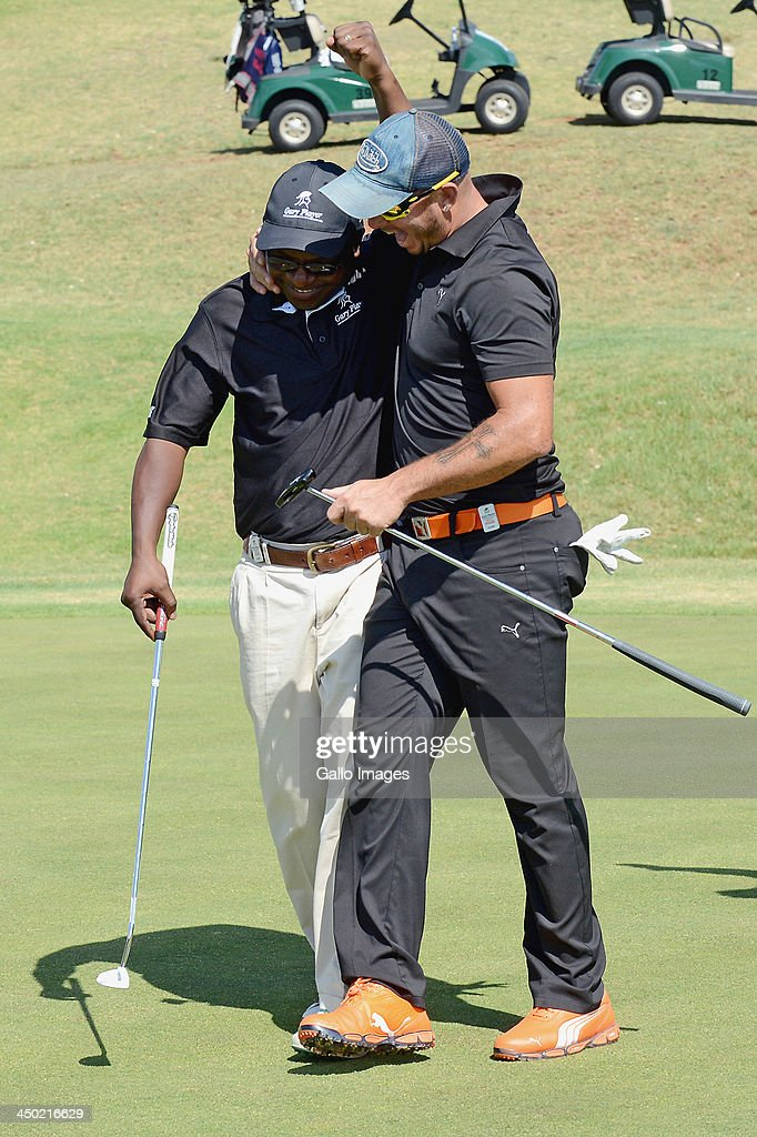 Mike Dladla (L) is congratulated by team-mate Herschelle Gibbs after sinking the winning putt during Round 2 of the Gary Player Invitational presented by Coca-Cola at The Lost City Golf Course on November 17, 2013 in Sun City, South Africa.