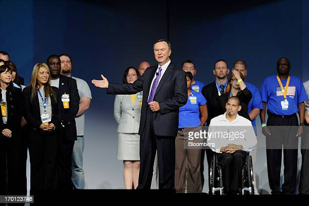 Mike Duke chief executive officer of WalMart Stores Inc center gestures while speaking the company's annual shareholders meeting in Fayetteville...
