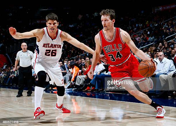 Mike Dunleavy of the Chicago Bulls drives against Kyle Korver of the Atlanta Hawks at Philips Arena on December 15 2014 in Atlanta Georgia NOTE TO...