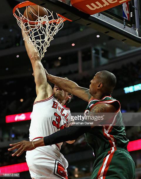 Mike Dunleavy of the Chicago Bulls is fouled across the face by Caron Butler of the Milwuakee Bucks during a preseason game at the United Center on...