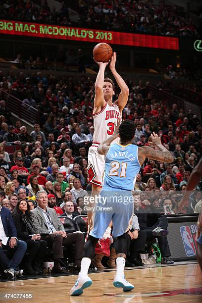 Mike Dunleavy of the Chicago Bulls shoots over Wilson Chandler of the Denver Nuggets on February 21 2014 at the United Center in Chicago Illinois...