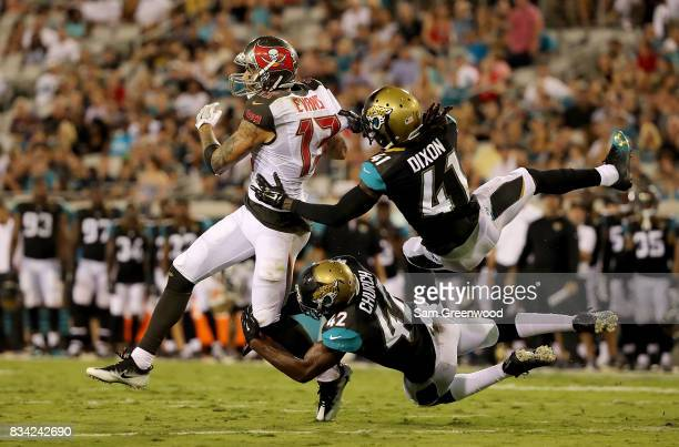 Mike Evans of the Tampa Bay Buccaneers is tackled by Brian Dixon and Barry Church of the Jacksonville Jaguars during a preseason game at EverBank...