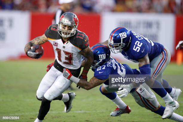 Mike Evans of the Tampa Bay Buccaneers runs for a first down after a catch against Darian Thompson and Jonathan Casillas of the New York Giants in...