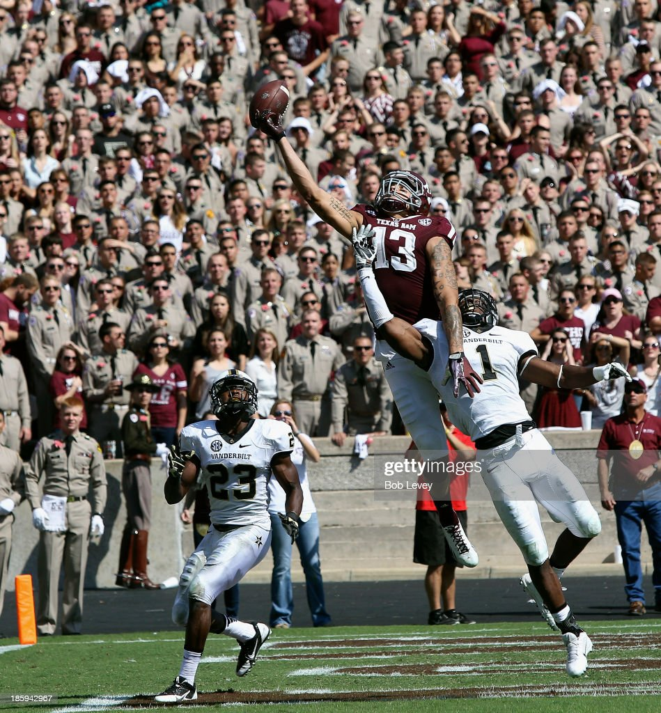 Mike Evans #13 of the Texas A&M Aggies has the ball go off his fingertips as he goes up between Kenny Ladler #1 of the Vanderbilt Commodores and Andre Hal #23 of the Vanderbilt Commodores in the second quarter at Kyle Field on October 26, 2013 in College Station, Texas.