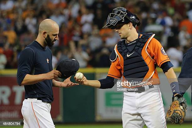 Mike Fiers of the Houston Astros takes a baseball from his catcher Jason Castro after tossing a nohitter en route to the Astros defeating the Los...