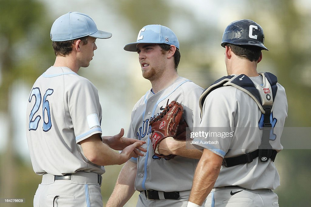 Mike Fischer #4 looks on as associate head coach Pete Maki #26 talks to David Spinosa #15 of the Columbia Lions during first inning action against the Miami Hurricanes on March 19, 2013 at Alex Rodriguez Park at Mark Light Field in Coral Gables, Florida. Miami defeated Columbia 9-6.