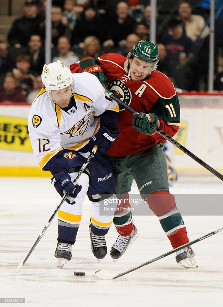 Mike Fisher #12 of the Nashville Predators and Zach Parise #11 of the Minnesota Wild go after the puck during the first period of the game on January 22, 2013 at Xcel Energy Center in St Paul, Minnesota.