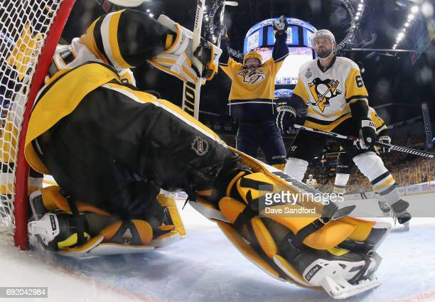 Mike Fisher of the Nashville Predators celebrates a goal by teammate James Neal as Ron Hainsey of the Pittsburgh Penguins reacts during the second...