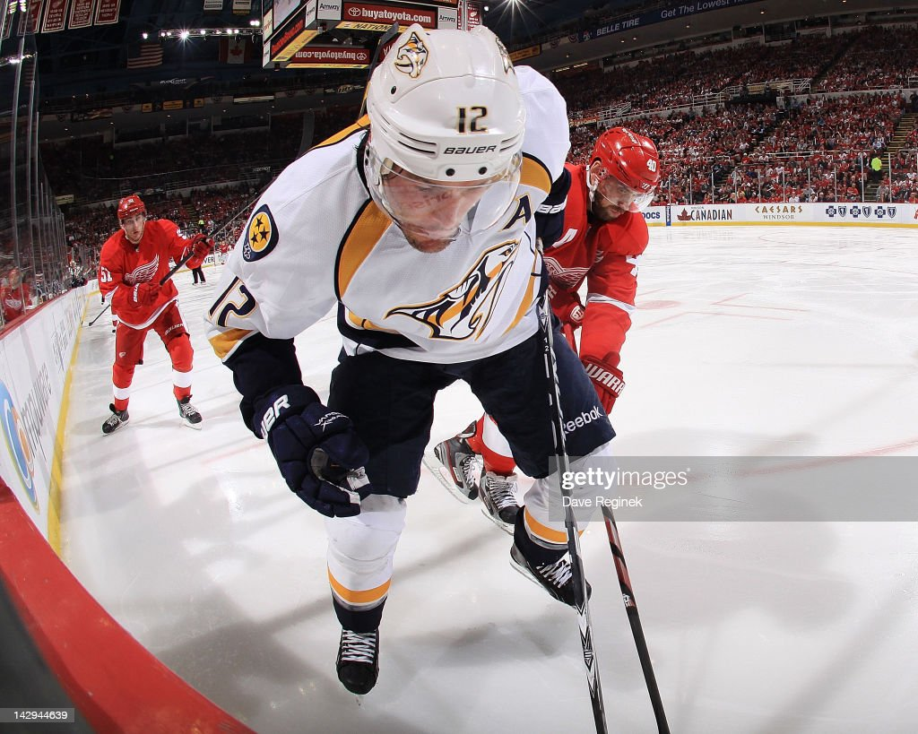<a gi-track='captionPersonalityLinkClicked' href=/galleries/search?phrase=Mike+Fisher&family=editorial&specificpeople=204732 ng-click='$event.stopPropagation()'>Mike Fisher</a> #12 of the Nashville Predators fights for the puck at the boards along with <a gi-track='captionPersonalityLinkClicked' href=/galleries/search?phrase=Henrik+Zetterberg&family=editorial&specificpeople=201520 ng-click='$event.stopPropagation()'>Henrik Zetterberg</a> #40 of the Detroit Red Wings in Game Three of the Western Conference Quarterfinals during the 2012 NHL Stanley Cup Playoffs at Joe Louis Arena on April 15, 2012 in Detroit, Michigan. Nashville wins 3-2 leading the series 2-1.