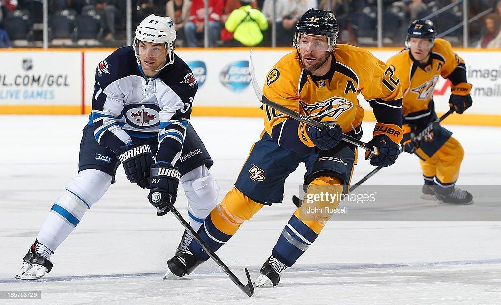 Mike Fisher #12 of the Nashville Predators skates against Michael Frolik #67 of the Winnipeg Jets at Bridgestone Arena on October 24, 2013 in Nashville, Tennessee.