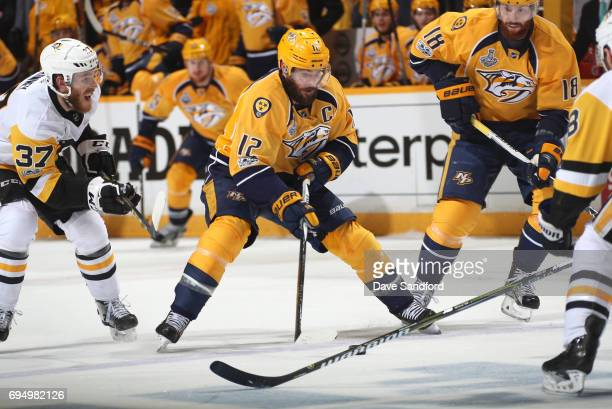 Mike Fisher of the Nashville Predators skates the puck into the offensive zone as Carter Rowney of the Pittsburgh Penguins pursues the play along...