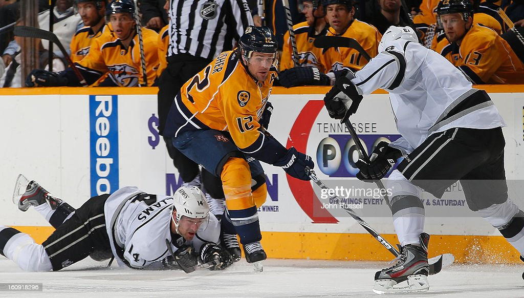 <a gi-track='captionPersonalityLinkClicked' href=/galleries/search?phrase=Mike+Fisher&family=editorial&specificpeople=204732 ng-click='$event.stopPropagation()'>Mike Fisher</a> #12 of the Nashville Predators skates with the puck against Justin Williams #14 and <a gi-track='captionPersonalityLinkClicked' href=/galleries/search?phrase=Jarret+Stoll&family=editorial&specificpeople=204632 ng-click='$event.stopPropagation()'>Jarret Stoll</a> #28 of the Los Angeles Kings during an NHL game at the Bridgestone Arena on February 7, 2013 in Nashville, Tennessee.