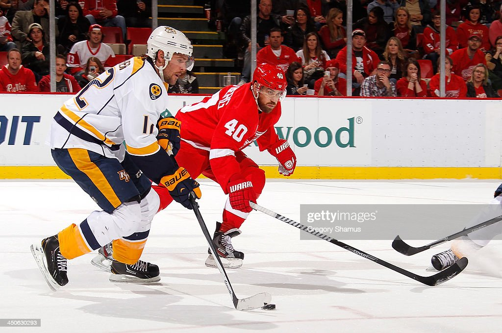 Mike Fisher #12 of the Nashville Predators tries to skate around the stick of Henrik Zetterberg #40 of the Detroit Red Wings during the first period at Joe Louis Arena on November 19, 2013 in Detroit, Michigan.
