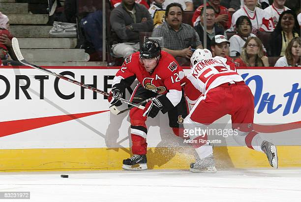 Mike Fisher of the Ottawa Senators battles along the boards for the puck against Niklas Kronwall of the Detroit Red Wings at Scotiabank Place on...