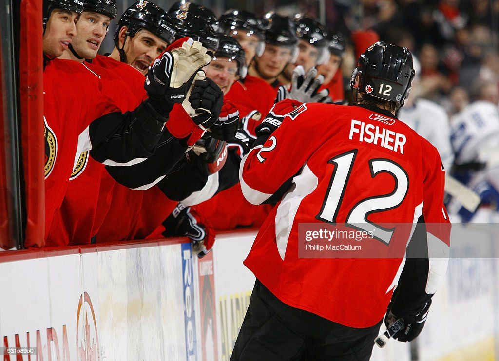 Mike Fisher of the Ottawa Senators celebrates his go ahead goal against the Toronto Maple Leafs with his teammates on the bench in a game at...