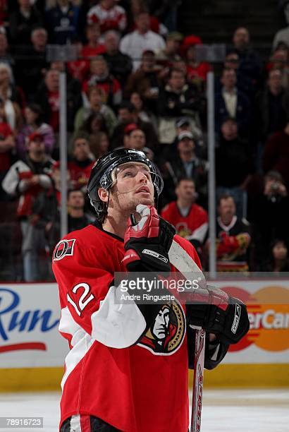 Mike Fisher of the Ottawa Senators looks up at a Steve Yzerman video presentation on the scoreboard prior to a game against the Detroit Red Wings at...