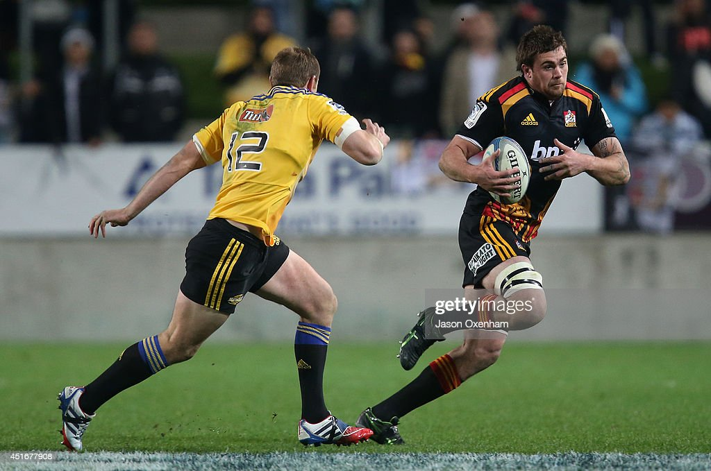Mike Fitzgerald of the Chiefs tries evade the defence of Hadleigh Parkes of the Hurricanes during the round 18 Super Rugby match between the Chiefs and the Hurricanes at Waikato Stadium on July 4, 2014 in Hamilton, New Zealand.