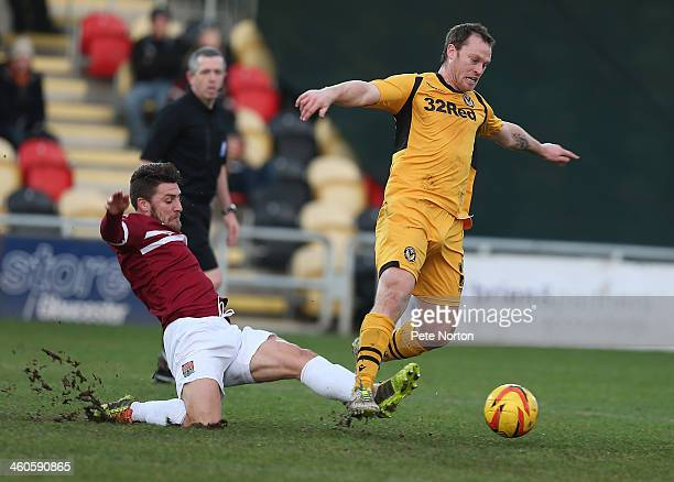 Mike Flynn of Newport County AFC moves away from the challenge of Gary Deegan of Northampton Town during the Sky Bet League Two match between Newport...