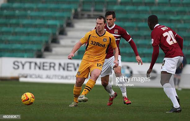Mike Flynn of Newport County AFC plays the ball watched by Darren Carter and David Moyo of Northampton Town during the Sky Bet League Two match...