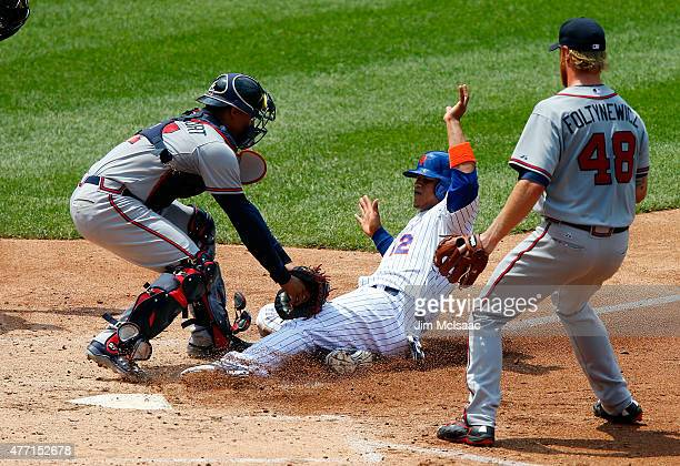 Mike Foltynewicz of the Atlanta Braves watches teammate Christian Bethancourt of the Atlanta Braves tag out Juan Lagares of the New York Mets during...