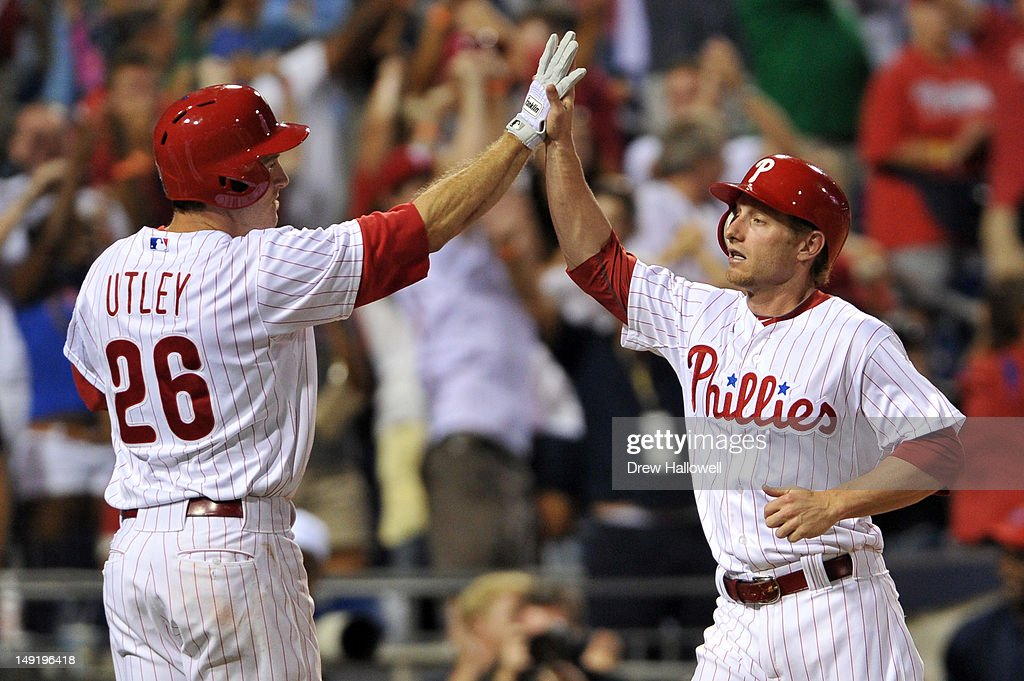 <a gi-track='captionPersonalityLinkClicked' href=/galleries/search?phrase=Mike+Fontenot&family=editorial&specificpeople=2493045 ng-click='$event.stopPropagation()'>Mike Fontenot</a> #18 of the Philadelphia Phillies high-fives teammate <a gi-track='captionPersonalityLinkClicked' href=/galleries/search?phrase=Chase+Utley&family=editorial&specificpeople=161391 ng-click='$event.stopPropagation()'>Chase Utley</a> #26 after scoring the game tying run against the Milwaukee Brewers at Citizens Bank Park on July 24, 2012 in Philadelphia, Pennsylvania. The Phillies won 7-6.