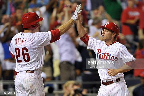 Mike Fontenot of the Philadelphia Phillies highfives teammate Chase Utley after scoring the game tying run against the Milwaukee Brewers at Citizens...