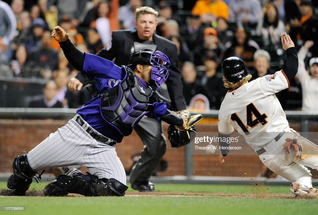 Mike Fontenot #14 of the San Francisco Giants beats the throw to the plate avoiding the tag of Wilin Rosario #12 of the Colorado Rockies in the eighth inning during an MLB baseball game at AT&T Park on September 26, 2011 in San Francisco, California. The Giants won the game 3-1.