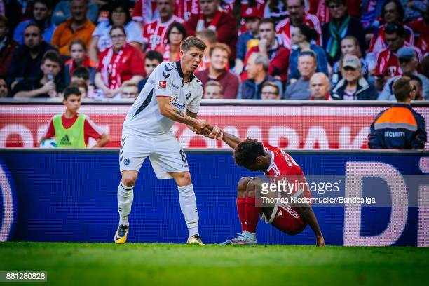 Mike Frantz of Freiburg helps David Alaba of Bayern up during the Bundesliga match between FC Bayern Muenchen and SportClub Freiburg at Allianz Arena...