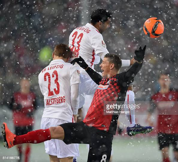 Mike Frantz of Freiburg jumps for a header with Marcel Halstenberg of RB Leipzig and Marvin Compper of RB Leipzig during the Second Bundesliga match...