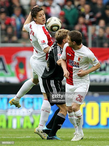 Mike Frantz of Nuernberg is challenged by Jens Hegeler and Daniel Baier of Augsburg during the Bundesliga play off leg two match between FC Augsburg...