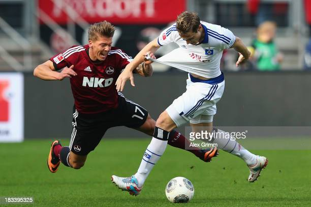 Mike Frantz of Nuernberg is challenged by Marcell Jansen of Hamburg during the Bundesliga match between 1 FC Nuernberg and Hamburger SV at Grundig...